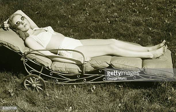 Woman sun tanning on meadow, (B&W), elevated view