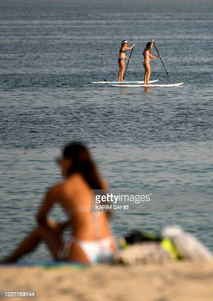 Woman sunbather sits along a beach as people stand up paddle board in the water in the Gulf emirate of Dubai on July 24, 2020. - After a painful...