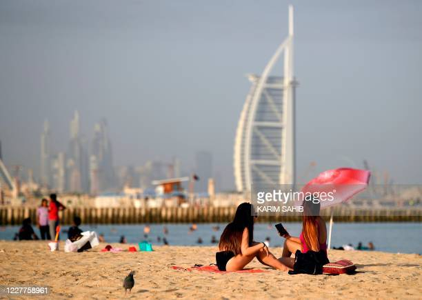 Woman sunbathers sit along a beach in the Gulf emirate of Dubai on July 24 while behind is seen the Burj al-Arab hotel. - After a painful four-month...