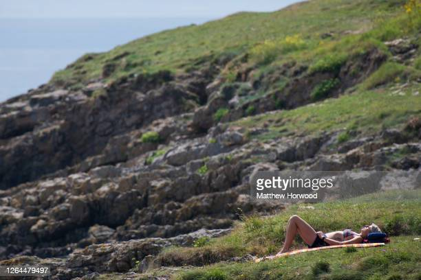 A woman sunbathes alone at Whitmore Bay Barry Island on August 7 in Barry Wales Forecasters have said Friday could be the hottest day of the year in...