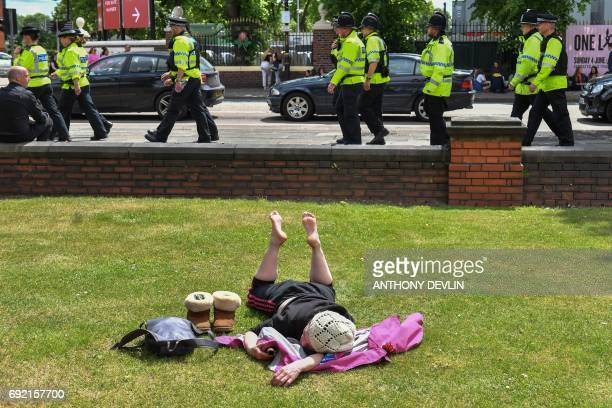 A woman sunbathes as police officers patrol around Old Trafford Cricket Ground ahead of the One Love Manchester tribute concert in Manchester on June...