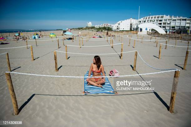 Woman sunbathes at 'Couchant or Sunset beach' in a roped off distancing zone marked out by the municipality along the beaches in La Grande Motte,...