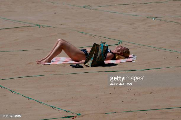 A woman sunbathes in a designated ropedoff area on Poniente Beach in Benidorm on June 21 a day after the town's beaches were reopened after three...
