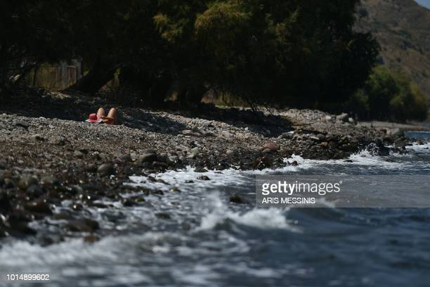 A woman sunbathes on a beach near the village of Skala Sykamineas on the Greek island of Lesbos on August 3 2018