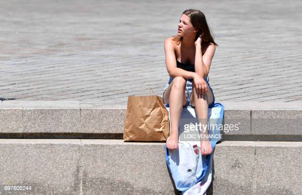 A woman sunbathes on June 19 2017 in Nantes western France as Meteo France has placed 16 departments on orange alert for heatwaves / AFP PHOTO / LOIC...