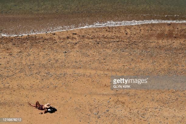 Woman sunbathes on Saltdean beach near Brighton on the south coast of England on June 2, 2020 following a further relaxation of the novel coronavirus...