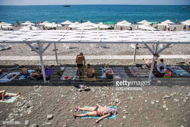 A woman sunbathes on the beach in front of the Fisht stadium in Sochi on June 14 on the eve of the Portugal v Spain match in the south Russian city