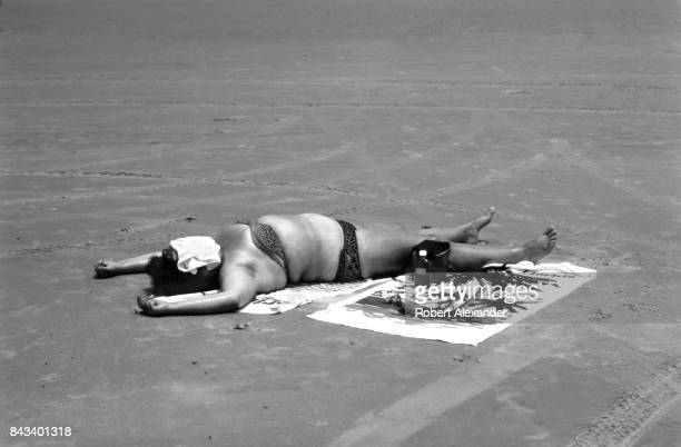A woman sunbathes on the beach near a lifeguard stand in Daytona Beach Florida in 1983