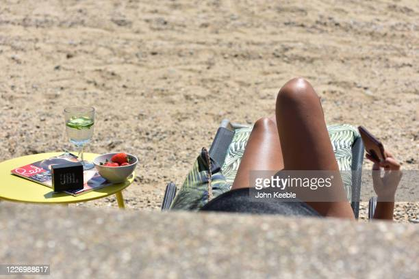 A woman sunbathes on the beach with a magazine strawberries and a drink on a warm and sunny May Day bank holiday on May 25 2020 in SouthendonSea...