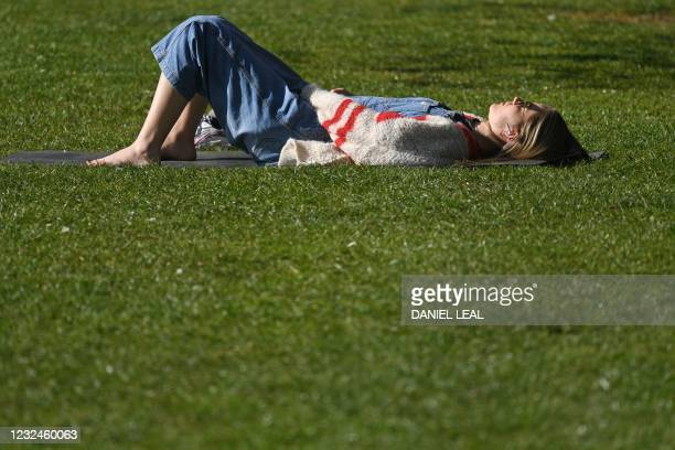Woman sunbathes on the grass in the Spring sunshine in Victoria Park, east London on April 22, 2021. - Under the relaxing of the Covid-19 rules,...