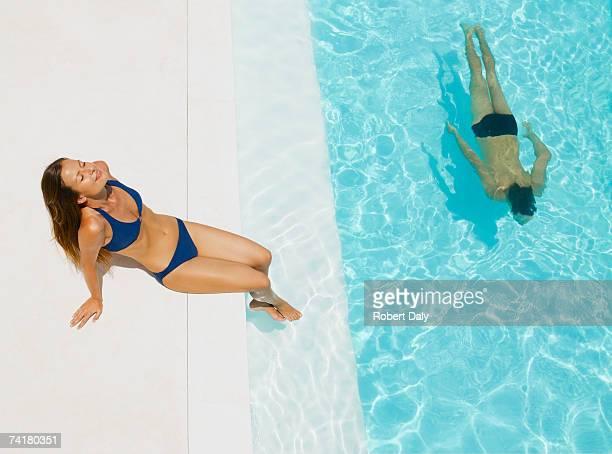 Hombre y una mujer tomando el sol en la piscina