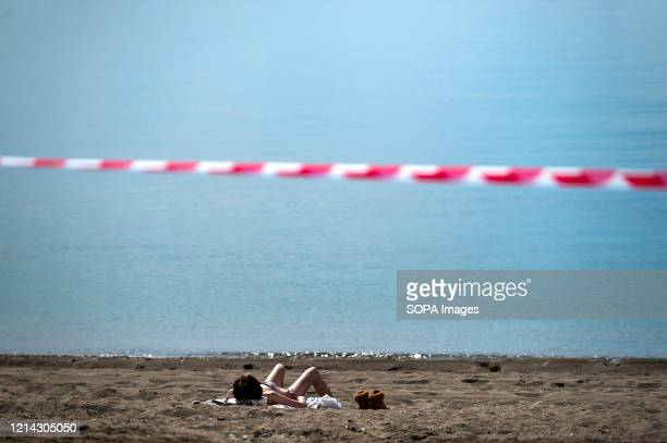 A woman sunbathing at Malagueta beach during a nationwide partial lockdown Spain is going through a plan of downscaling towards a new normality by...
