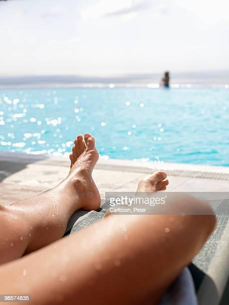 Woman sunbathing by a swimming-pool, Turkey.