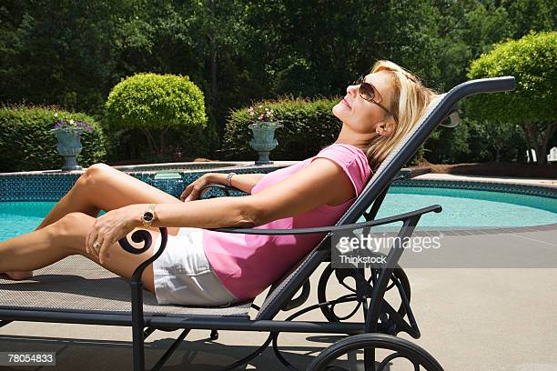 Woman sunbathing by pool