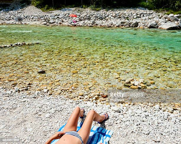 woman sunbathing by river in bikini