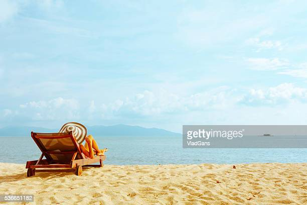 woman sunbathing in beach chair - outdoor chair stock pictures, royalty-free photos & images