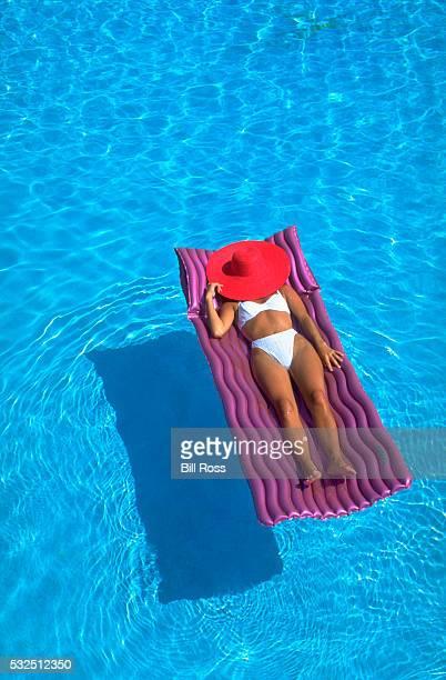 Woman Sunbathing in Pool
