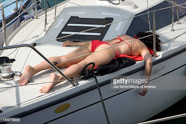 Woman sunbathing in red swimming suit on boat deck in Portoferraio, Province of Livorno, on the island of Elba in the Tuscan Archipelago of Italy,...