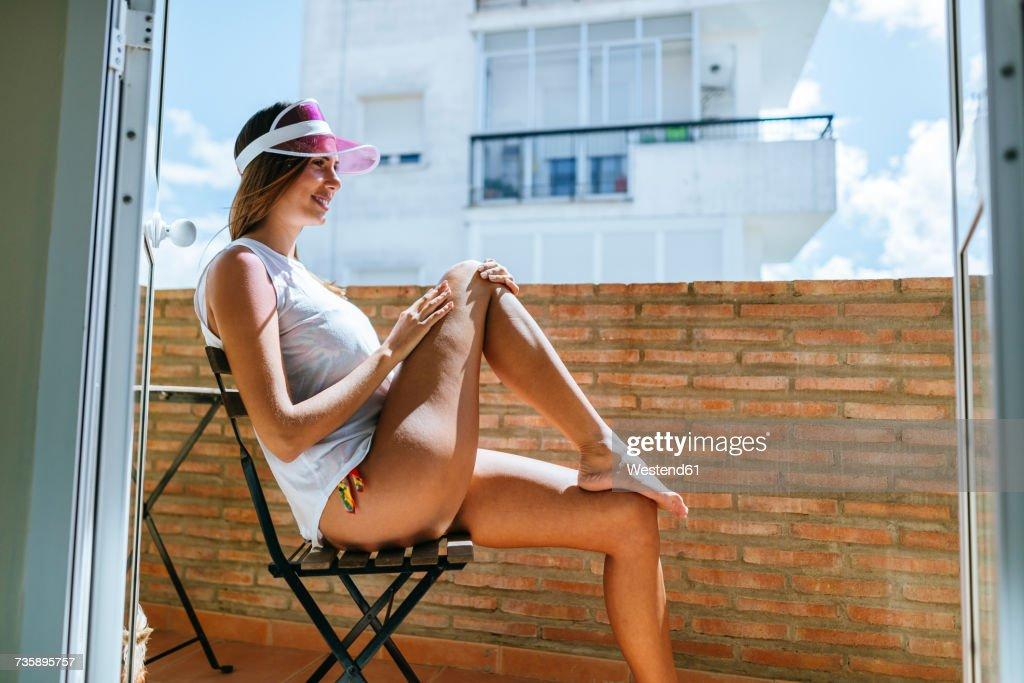 Woman sunbathing on a balcony : Stock Photo