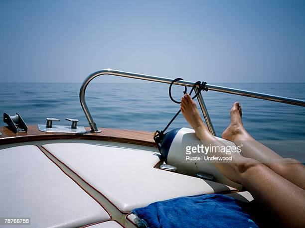 a woman sunbathing on a boat deck - ponte di una nave foto e immagini stock