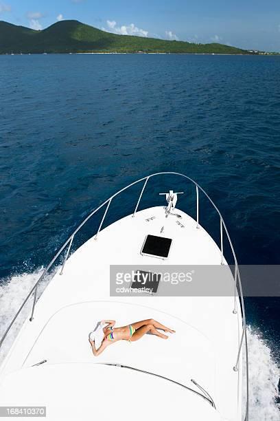 Femme au soleil sur un yacht de luxe en arrivant à l'île des Caraïbes