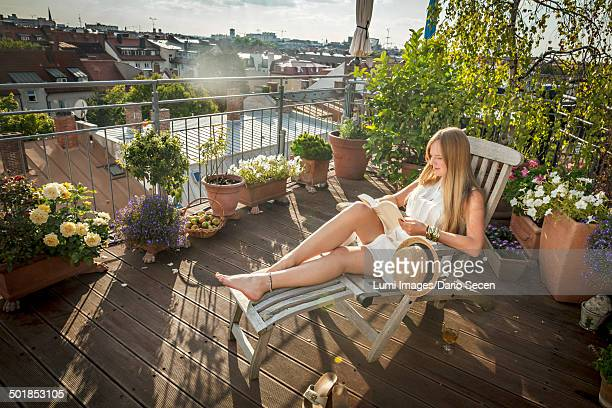 woman sunbathing on balcony, munich, bavaria, germany, europe - バルコニー ストックフォトと画像