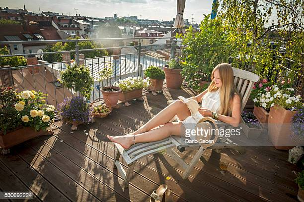 woman sunbathing on balcony, munich, bavaria, germany, europe - bavière photos et images de collection
