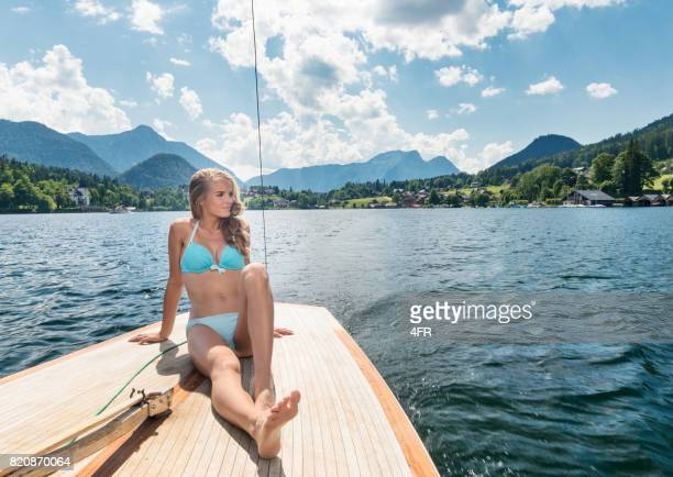 Woman sunbathing on deck of a sailboat