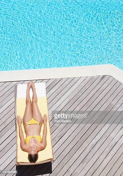 Woman sunbathing on deck outdoors