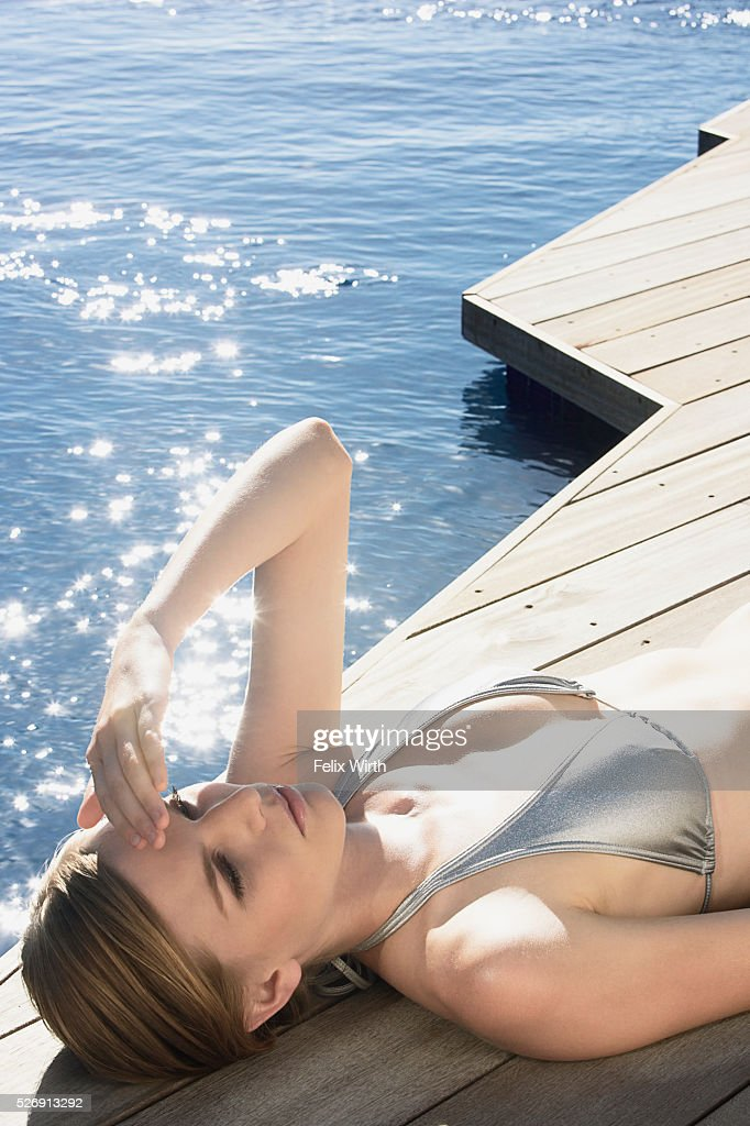 Woman sunbathing on deck : Stock Photo
