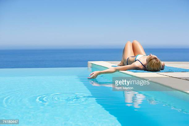 woman sunbathing on deck with infinity pool - poolside stock pictures, royalty-free photos & images
