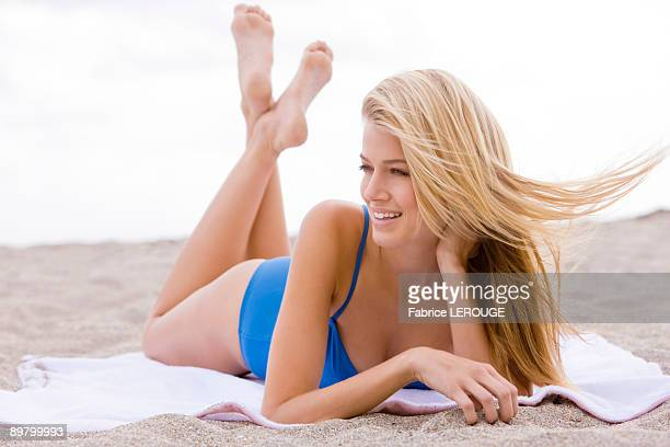 woman sunbathing on the beach - pés cruzados - fotografias e filmes do acervo