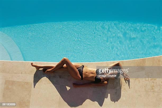 Woman sunbathing on the edge of swimming pool