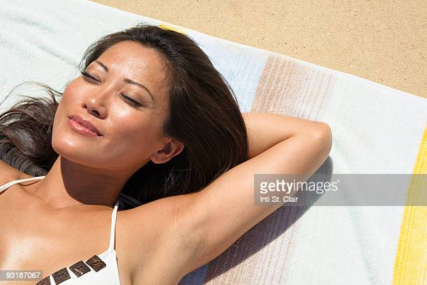 Woman sunbathing on towel at beach