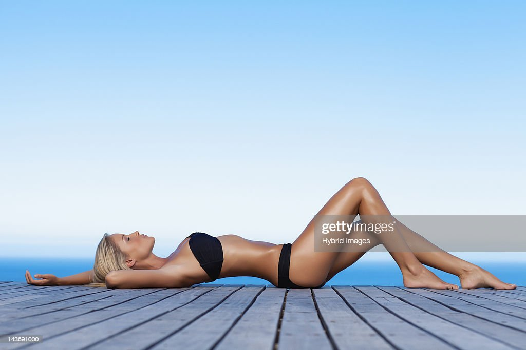 Woman sunbathing on wooden pier : Stock Photo