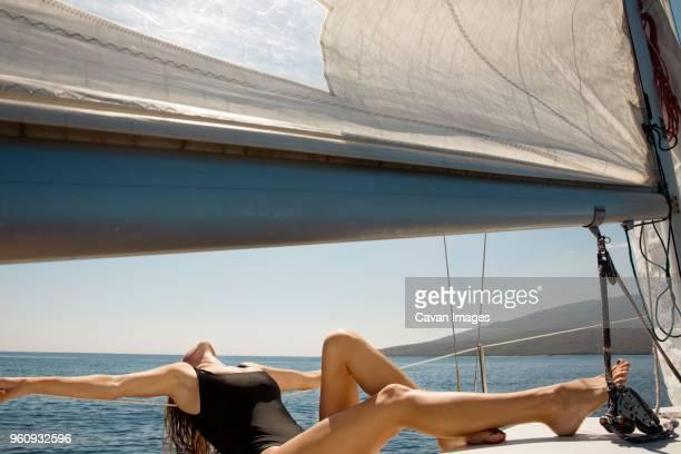 Woman sunbathing on yacht sailing in sea