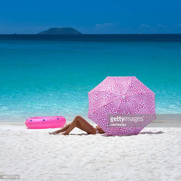 Mulher tomando banho de sol com guarda-chuva em Trunk Bay Beach, St.John, Ilhas Virgens dos Estados Unidos