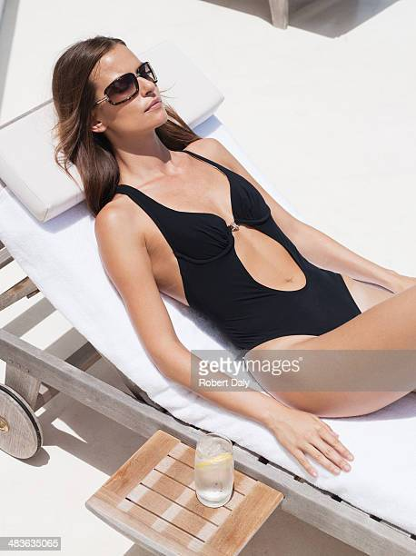 woman sunbathing with sunglasses - women sunbathing pool stock photos and pictures