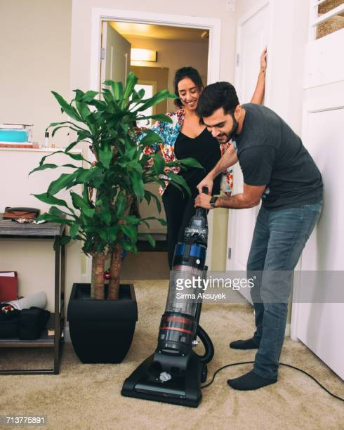 woman supervising man vacuuming carpet - role reversal stock photos and pictures