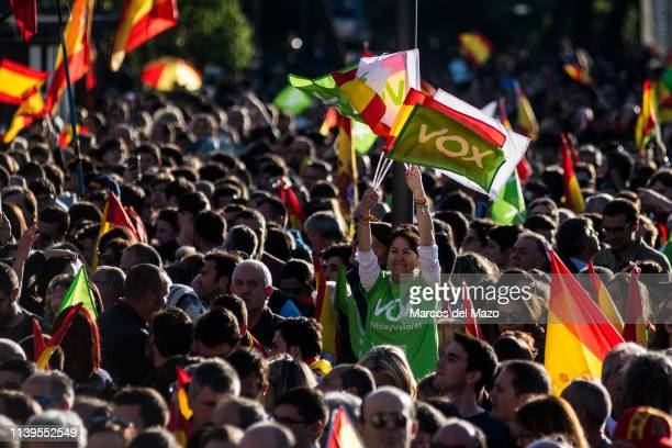 A woman supporter of far right wing party VOX waving flags during the closing campaign rally ahead of the general elections that will take place in...