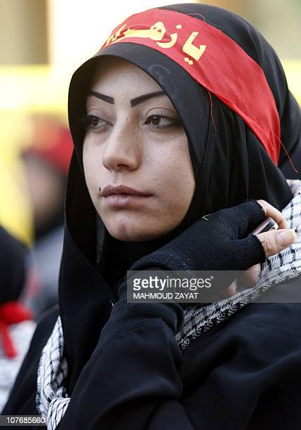 A woman supporter of the Shiite Muslim Hezbollah movement watches a Hezbollah parade in the city of Nabatiyeh in southern Lebanon on December 19 to...