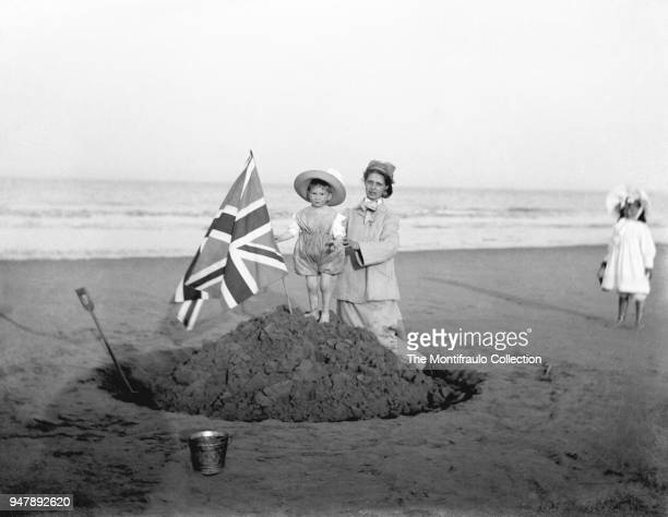 A woman supporting a young child holding a Union Jack flag as he stands on top of a sandy hill by the sea in celebration of Queen Victorias Jubilee...