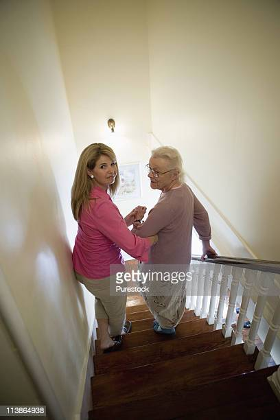 Woman supporting and helping senior woman down the stairs