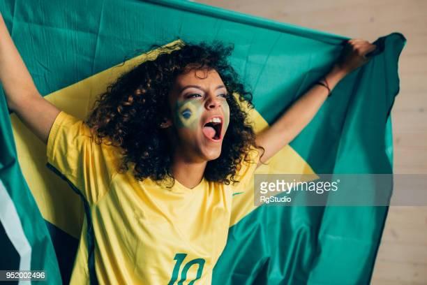 mulher, apoiando a seleção de futebol brasileiro, segurando uma bandeira sobre a cabeça em emoção - camisa de futebol - fotografias e filmes do acervo