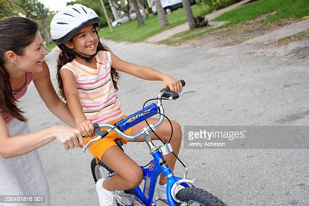 woman supporting daughter (7-9) learning to ride bicycle in street - cycling helmet stock pictures, royalty-free photos & images