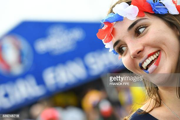 TOPSHOT A woman supporting France smiles prior to the Euro 2016 group A football match between France and Romania at Stade de France in SaintDenis...