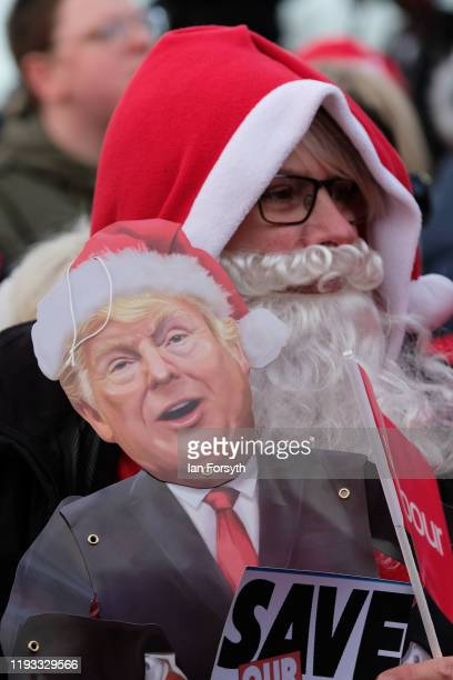 A woman supporting the NHS and dressed as Santa Claus listens to speeches as she joins other supporters during a stump speech event at the Sporting...