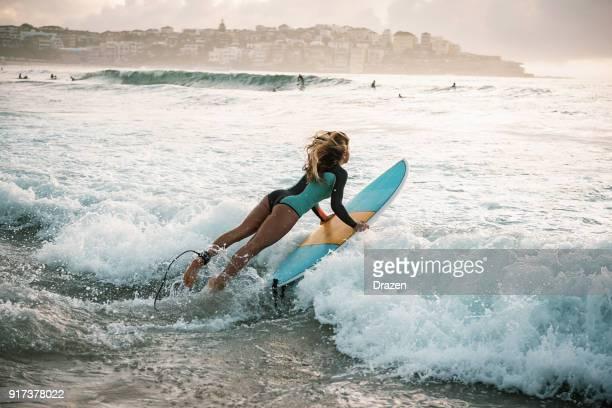 springt frau surfer in den wellen - brandung stock-fotos und bilder