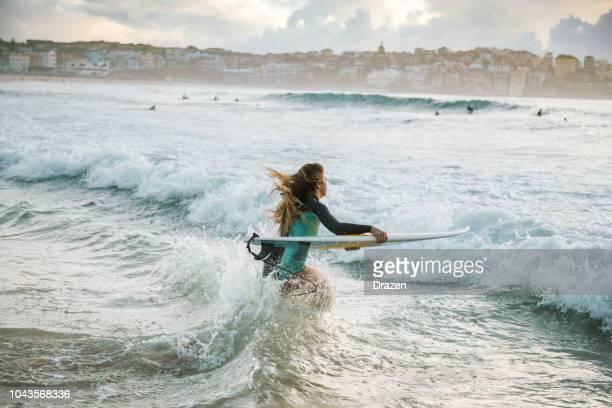 frau surfer springt auf ihr surfbrett in der welle - extremsport stock-fotos und bilder