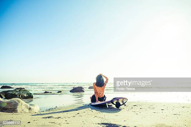 a woman surfer sits on her surfboard, at the beach, looking out to the ocean in california - robb reece bildbanksfoton och bilder
